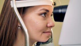 Een vrouw leunt vooruit om haar die ogen te hebben door een medische machine worden getest stock video