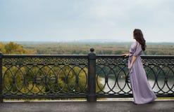 Een vrouw in een lichtpaarse kleding die de afstand onderzoeken, Royalty-vrije Stock Afbeeldingen