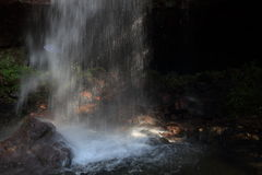 Een vrouw liep met een paraplu lopend in het hol achter de waterval Royalty-vrije Stock Fotografie
