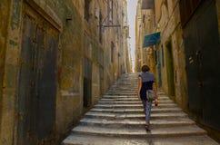 Een vrouw loopt door de straat van Valletta Stock Afbeeldingen