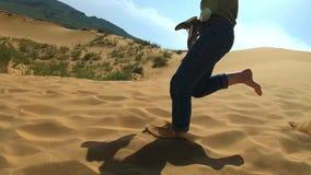 Een vrouw loopt langs het zand in de woestijn Een meisje loopt blootvoets op een zandduin in het zand stock video
