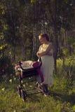 Een vrouw loopt met een babywandelwagen Royalty-vrije Stock Foto's