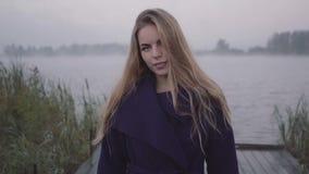 Een vrouw loopt rechtstreeks in de camera en met een arrogante blik, bekijkt de achtergrond van een meer met mist stock video