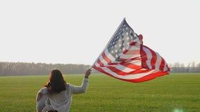 Een vrouw loopt snel over het gebied met een grote vlag stock videobeelden