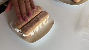Een vrouw maakt een cake Legt savoiardikoekjes in lagen in een mengsel met room stock footage