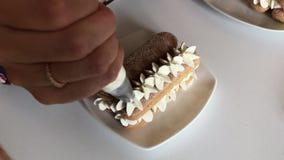 Een vrouw maakt een cake Legt savoiardikoekjes in lagen in een mengsel met room Past room toe gebruikend een gebakjezak stock video