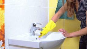 Een vrouw maakt een gootsteen schoon stock footage
