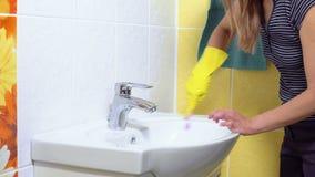 Een vrouw maakt een gootsteen schoon stock videobeelden
