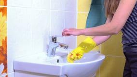 Een vrouw maakt een gootsteen schoon stock video