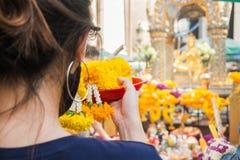 Een vrouw maakt plechtig dienstenaanbod van bloemenslingers royalty-vrije stock fotografie