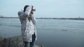Een vrouw maakt spruit op oude uitstekende retro stijlcamera naast de vijver stock videobeelden