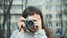 Een vrouw maakt spruit op oude uitstekende retro stijlcamera in stedelijk milieu stock footage
