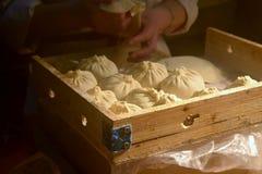 Een vrouw maakt tot gist Chinese bollen` bao zi ` die met vlees en groente wordt gevuld stock afbeeldingen