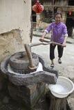 Een vrouw maalt sojabonen om melk te produceren Royalty-vrije Stock Afbeelding
