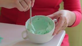 Een vrouw mengt roomkaas met voedselkleuring Alvorens eenvormige kleuring te geven Kleurende room voor smering van de cake stock videobeelden