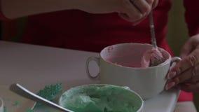 Een vrouw mengt roomkaas met voedselkleuring Alvorens eenvormige kleuring te geven Kleurende room voor smering van de cake stock video