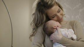 Een vrouw met een baby in haar wapens stock footage