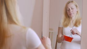 Een vrouw met blonde haarzitting voor een spiegel in een rode plastic kom bereidt een mengsel voor om haar te verlichten stock footage