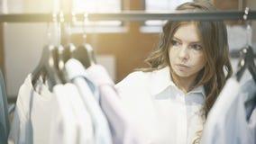 Een vrouw met bruin haar kiest te kopen kleren Ontwerperwinkel Stock Foto