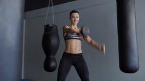 Een vrouw met een atletisch lichaamspakhuis is bezet met een spiersimulator stock videobeelden