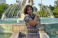 Een vrouw met een kat in haar wapens Stock Foto's