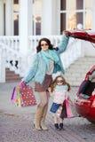 Een vrouw met een kind na het winkelen lading de auto Stock Afbeelding