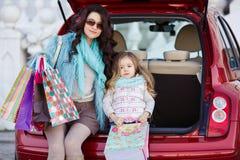 Een vrouw met een kind na het winkelen lading de auto Royalty-vrije Stock Fotografie