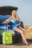 Een vrouw met een koffer dichtbij de auto Stock Afbeeldingen