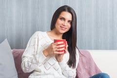 Een vrouw met een rode mok in haar handen, glimlachenzittingen op de laag, bank bekijkt camera Stock Afbeeldingen