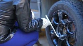 Een vrouw met glazen en handschoenen maakt een autoband met een moersleutel vast stock footage