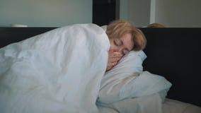 Een vrouw met een griep, slecht voelen die, in haar die neus blazen, in een witte deken wordt verpakt Artsen` s medische hulp stock video