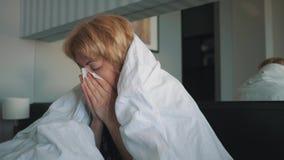 Een vrouw met een griep, slecht voelen die, in haar die neus blazen, in een witte deken wordt verpakt Artsen` s medische hulp stock footage