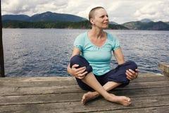 Een vrouw met haarverlies van chemotherapiebehandeling zit buiten op een dok met de oceaan en bergen achter haar Stock Fotografie
