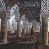 Een vrouw met een headscarf bidt in Nasir Al-Mulk Mosque in Shiraz, Iran, als Roze Moskee ook wordt bekend die stock foto