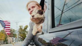 Een vrouw met een hond en een Amerikaanse vlag kijkt uit het autoraam Zij reist langs de Amerikaanse voorsteden Reis stock video