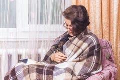Een vrouw met een katje in haar handen leest een boek De vrouwenomslag stock afbeelding