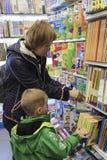 Een vrouw met een kind kiest een boek in een boekhandel stock foto's