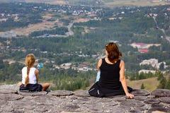 Een Vrouw met een kind zit op de rand van een klip en een rust stock afbeeldingen