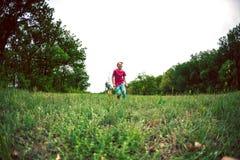 Een vrouw met kindlooppas langs het gras Royalty-vrije Stock Foto's