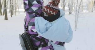 Een vrouw met een klein kind loopt door het park in de winter stock videobeelden