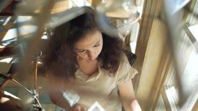 Een vrouw met krullend haar zit dichtbij een venster in een koffie en doorbladert een krant Mening van hierboven stock videobeelden