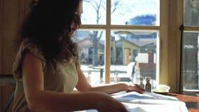 Een vrouw met krullend haar zit dichtbij een venster in een koffie en leest een krant stock videobeelden