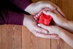 Een vrouw met een man die een gift in zijn hand op een houten achtergrond op de Dag van Valentine of bij Kerstmis houden royalty-vrije stock foto's