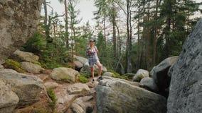 Een vrouw met een rugzak op haar gaat op reusachtige stenen in het bos het Lopen en actieve levensstijl achteruit stock video