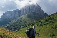 Een vrouw met een rugzak in een vest en hoedenplanken op alpien en bekijkt de berg Aceshbok stock foto's