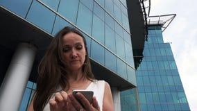 Een vrouw met een telefoon dichtbij het commerciële centrum stock video