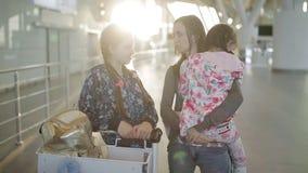 Een vrouw met twee dochters die de kar van de bagagehand met zakken langs luchthavenzaal trekken Passagiers op wachtend gebied stock footage