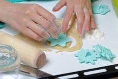 Een vrouw met een zegel past ornament op ronde spaties van gerold deeg toe Voor het maken van heemstsandwiches stock foto's