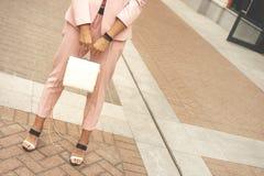 Een vrouw in modieuze bleke pantsuit - roze stoffige kleur stock foto