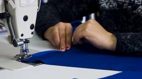 Een vrouw naait kleren bij een naaiende fabriek 1 Stock Afbeeldingen